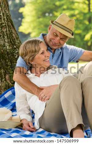 Happy elderly wife and husband hugging in park - stock photo