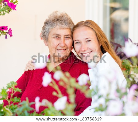 Happy elderly woman and her helpful assistant - stock photo
