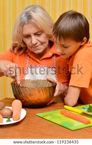 Happy elderly woman and the boy in the orange in the kitchen - stock photo