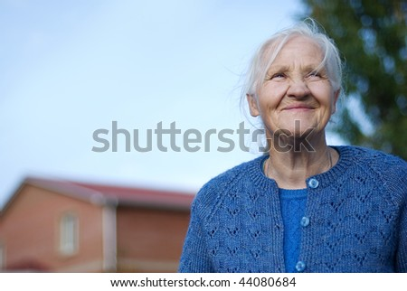 Happy elderly woman, building on the background - stock photo