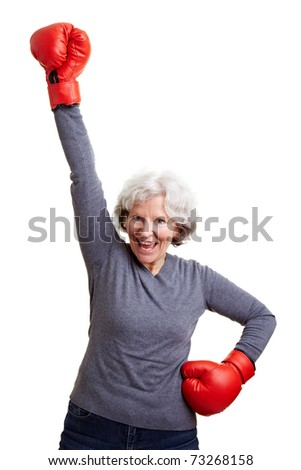 Happy elderly woman cheering with red boxing gloves - stock photo