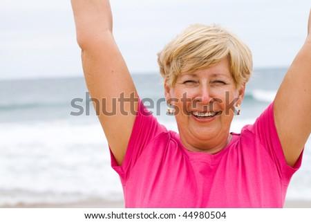 happy elderly woman doing exercise on beach - stock photo