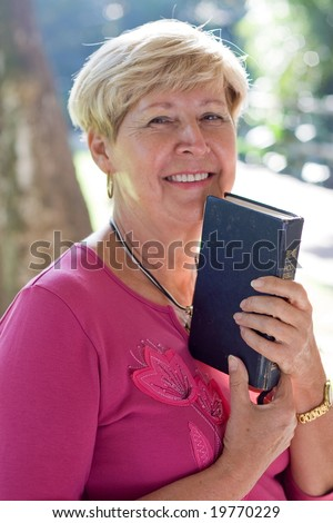 happy elderly woman holding a bible - stock photo