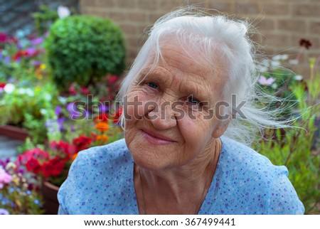Happy elderly woman in her flower garden - stock photo