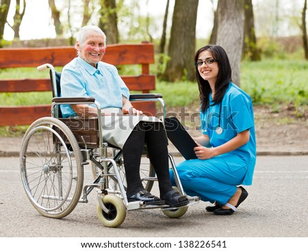 Happy elderly woman in wheelchair and kind nurse outdoors. - stock photo
