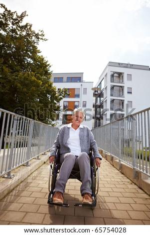 Happy elderly woman in wheelchair using a ramp - stock photo