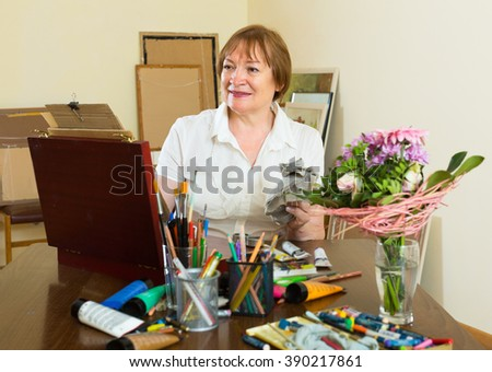 Happy elderly woman painting for fun at home - stock photo