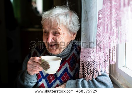 Happy elderly woman portrait sitting at the table and drink tea. - stock photo