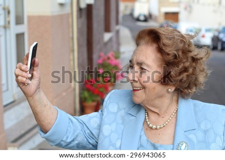 Happy elderly woman reading emails on smart phone at home