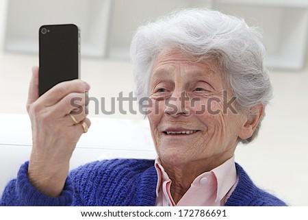 Happy elderly woman selfie herself with her smart phone  - stock photo