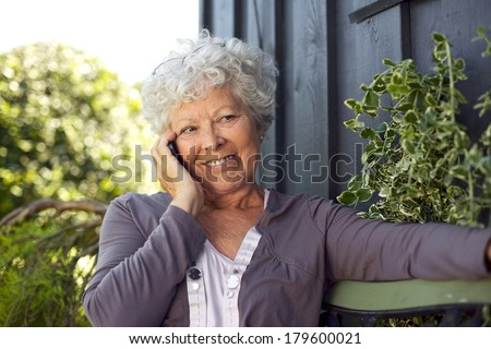 Happy elderly woman sitting on a bench in backyard talking on mobile phone and smiling - stock photo