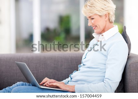 happy elderly woman using laptop computer at home - stock photo