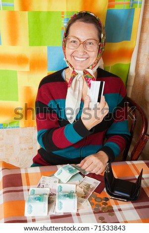 Happy elderly woman with  credit card  and money at her home