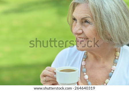 Happy elderly woman with cup of coffee - stock photo