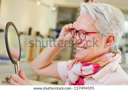 Happy elderly woman with new glasses looking in a mirror at optician store