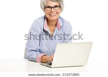 Happy elderly woman working in the office with a laptop - stock photo