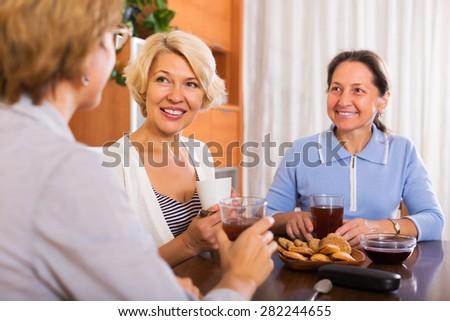Happy elderly women having coffee break at office. Focus on blonde woman - stock photo