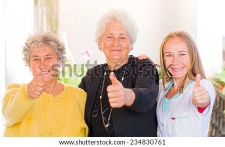Happy elderly women with their carer showing thumbs up - stock photo