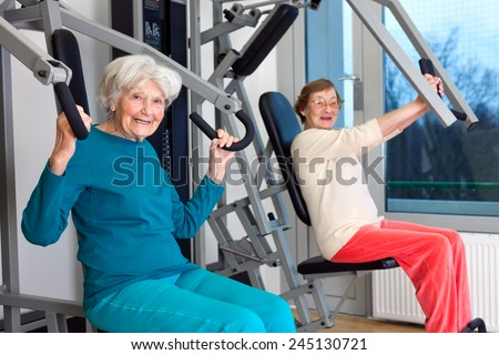 Happy Elderly Women Working Out at the Fitness Gym While Looking at the Camera. - stock photo