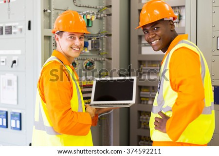 happy electrical co-workers using laptop computer checking transformer control box - stock photo