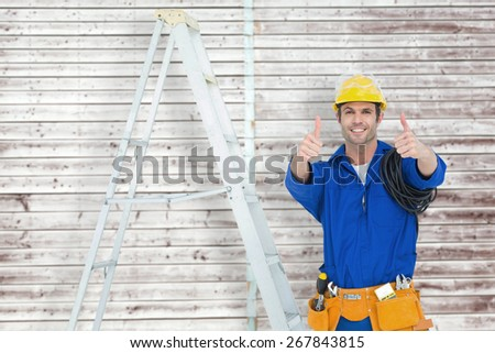 Happy electrician gesturing thumbs up by ladder against digitally generated grey wooden planks - stock photo