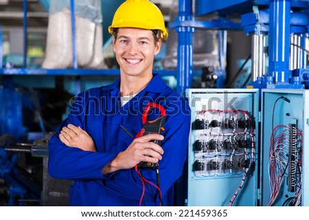 happy electrician holding digital insulation resistance tester - stock photo