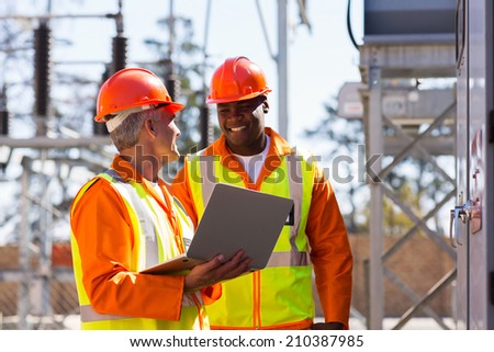 happy electricians using laptop computer in electrical substation - stock photo