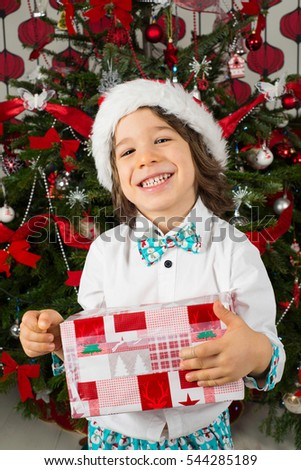 Happy elegant three years boy holding Christmas present