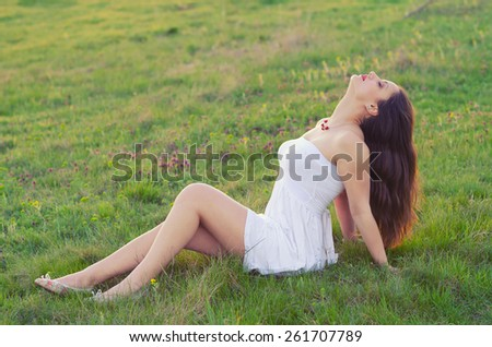 Happy elegant woman sitting on the meadow on beautiful spring day. - stock photo