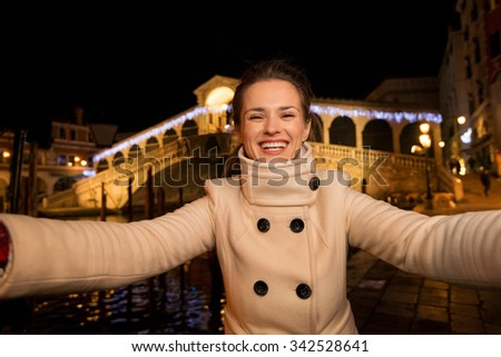 Happy elegant young woman in white coat taking selfie while standing in front of Rialto Bridge in the evening. She having Christmas time trip and enjoying stunning views of Venice, Italy - stock photo