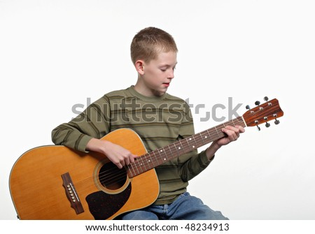 happy elementary age child sitting and playing a large acoustic guitar - stock photo