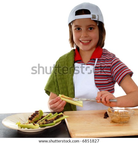 """Happy elementary girl making """"ants on a log,"""" a healthy, fun snack. - stock photo"""