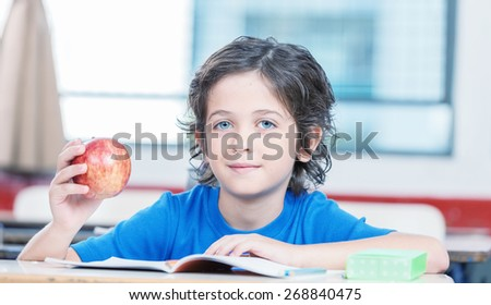 Happy elementary pupil touching his apple and reading book. - stock photo