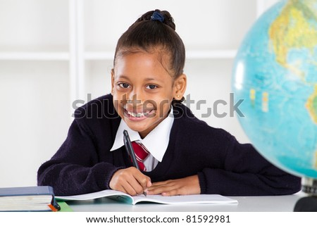 happy elementary school girl in classroom - stock photo