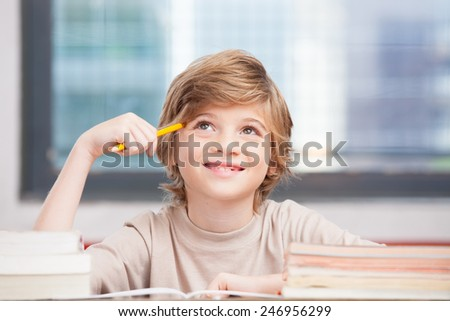 Happy elementary schoolboy thinking about ideas for schoolwork. - stock photo