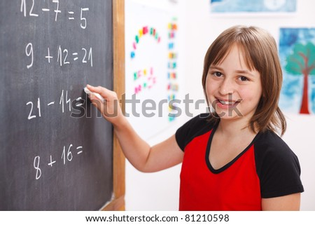 Happy elementary schoolgirl writing equation solution on chalkboard - stock photo
