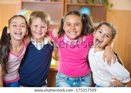 Happy elementary students in classroom at school - stock photo