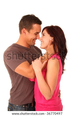 Happy embracing beautiful young couple against white background