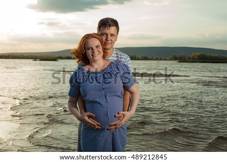 Happy embracing couple. Hot summer evening on the background.