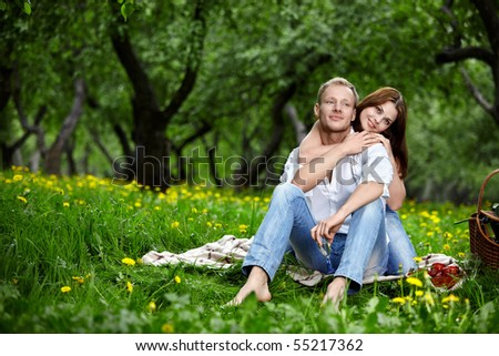Happy embracing couple in park in the foreground - stock photo
