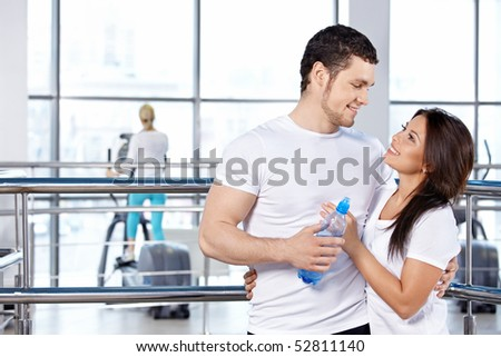 Happy embracing young couple in fitness club - stock photo