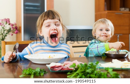 happy  emotional baby girls eating food at wooden table - stock photo