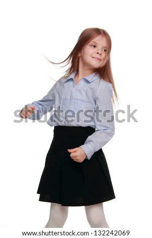 Happy emotional little girl in modern school uniform and healthy long hair dancing and having fun on white background - stock photo