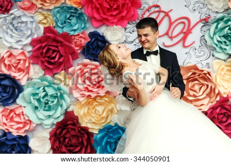 Happy emotional wedding couple holding hands and smiling groom and beautiful bride with flowers background - stock photo