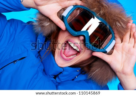 happy emotional woman in ski glasses and winter coat