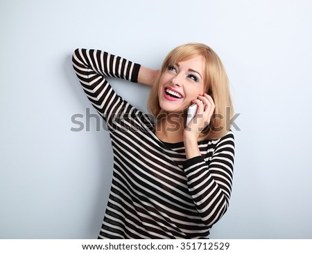Happy emotional young blond woman talking on mobile phone and looking up on blue background
