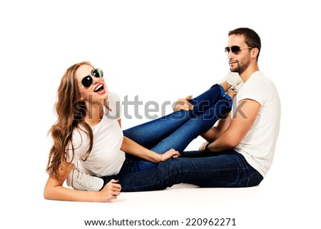 Happy emotional young couple in love posing at studio. Isolated over white. - stock photo