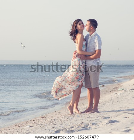 happy emotive adult couple on the sea shore.  copy space. White sand, blue water, seagulls - stock photo