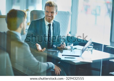 Happy employee discussing idea to colleague in office - stock photo