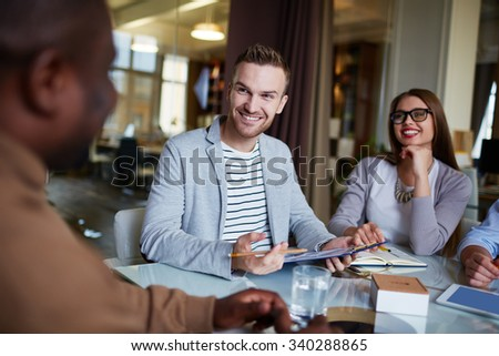 Happy employee looking at his colleague during explanation - stock photo